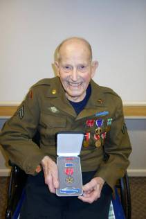 Retired veterinarian Lauren Brown displays one of his overdue military medals from World War II.